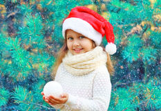 Christmas portrait smiling child little girl in santa red hat holding snowball near branch tree Royalty Free Stock Image