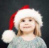 Christmas Portrait of Smiling Little Girl. Child in Santa Hat Stock Photo