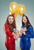 Christmas portrait of smiling women in luxurious dress holding little pigs. Christmas and New Year concept.  stock images