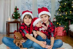 Christmas portrait of three brothers with Santa hats sitting on stock photography