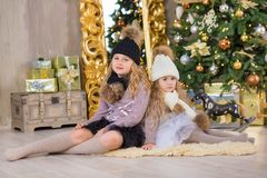 Christmas portrait of two beautyful cute girls Smiling sisters friends and xmas luxury green white tree in unique interior studio Stock Photo
