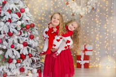 Christmas portrait of two beautyful cute girls Smiling sisters friends and xmas luxury green white tree in unique interior studio royalty free stock photography
