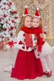 Christmas portrait of two beautyful cute girls Smiling sisters friends and xmas luxury green white tree in unique interior studio Stock Image