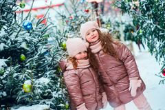 Christmas portrait of two happy sisters playing outdoor in winter snowy city decorated for New Year holidays. Kids spending Christmas vacations outdoor and stock images