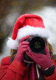 Christmas portrait of a woman with photo camera Stock Photos