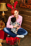 Christmas portraite of a red hair girl and her dog. Red-haired girl with red antlers holding a dog on her lap and sitting on a sled in a country house with Royalty Free Stock Photography