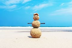 Christmas positive Sandy Snowman in red Santa Claus hat at ocean sunset beach. New Year vacation discounts in hot countries destinations concept Royalty Free Stock Photography