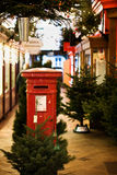 Christmas Post. Royal Mail UK mail box in an indoor market with Christmas trees Royalty Free Stock Photos