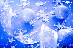 Christmas postcard with curly ribbon, decorative balls, snowflakes and snow effect. royalty free stock image