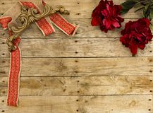 Christmas postcard frame on wooden background for greeting card. Red ribbon with vintage wooden ornament and big flowers. Xmas. Christmas frame. Red ribbon with stock photography