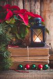 Christmas postcard with Poinsettia on the old books with fir tree, cones and toys balls and burning lantern. Toned Stock Photo