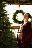 Christmas Pregnancy 2. Laughing pregnant mom in front of christmas tree Stock Photography