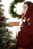 Christmas Pregnancy 3. Hooded pregnant mother in front of tree Stock Photos