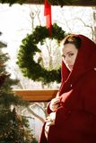 Christmas Pregnancy. Pregnant mother in red coat poses by a tree Stock Images