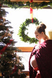 Christmas Pregnancy. Pregnant mother in front of a christmas tree Stock Image
