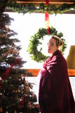 Christmas Pregnancy 4. Pregnant mother wrapped in a red velvet blanket in front of a christmas tree Stock Images