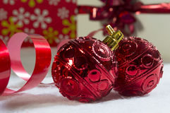 Christmas prep. Twin red baubles up close with ribbon and gifts royalty free stock photos