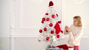 Christmas preparation. Blonde woman holding red Christmas ball at white Christmas tree. Christmas decorations. stock footage