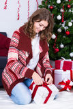 Christmas preparation concept - happy woman wrapping Christmas p Stock Image