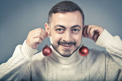 Christmas preparation. Christmas and new year concept. Cheeful man holding tree balls and smiling. Christmas preparation Stock Photos