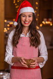 Christmas preparations. Christmas baking santa woman smiling happy having fun with Christmas preparations wearing Santa hat stock photos