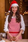 Christmas preparations. Christmas baking santa woman smiling happy having fun with Christmas preparations wearing Santa hat stock photo