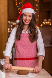 Christmas preparations. Christmas baking santa woman smiling happy having fun with Christmas preparations wearing Santa hat royalty free stock image