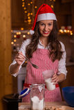 Christmas preparations. Christmas baking santa woman smiling happy having fun with Christmas preparations wearing Santa hat Stock Images