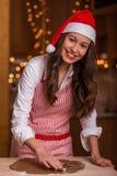 Christmas preparations. Christmas baking santa woman smiling happy having fun with Christmas preparations wearing Santa hat royalty free stock photography