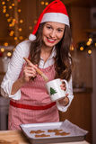 Christmas preparations. Christmas baking santa woman smiling happy having fun with Christmas preparations wearing Santa hat Stock Photography