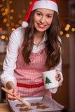 Christmas preparations. Christmas baking santa woman smiling happy having fun with Christmas preparations wearing Santa hat Royalty Free Stock Photo