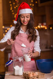 Christmas preparations. Christmas baking santa woman smiling happy having fun with Christmas preparations wearing Santa hat Royalty Free Stock Photography