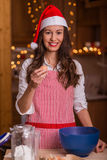 Christmas preparations. Christmas baking santa woman smiling happy having fun with Christmas preparations wearing Santa hat Stock Photo