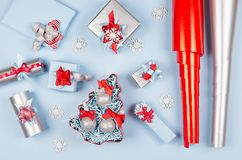 Christmas preparations - festive different gift boxes in red, blue and metallic color with silk ribbons, wrapping paper. royalty free stock image