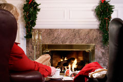 Christmas preparations at home. Getting ready for Christmas - woman has tea by the fire Royalty Free Stock Photo