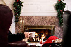 Christmas preparations at home. Woman holding tea cup by the living room fire Royalty Free Stock Photography