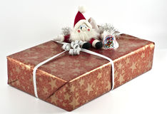 Christmas present. Red Christmas present with a santa doll and some jingle bells on top Royalty Free Stock Photography
