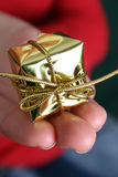 Christmas Present. Small Golden christmas decoration held in the palm Royalty Free Stock Photo