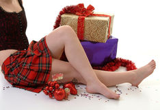 Christmas Present. Young female in tartan skirt sitting with christmas parcels Royalty Free Stock Photos