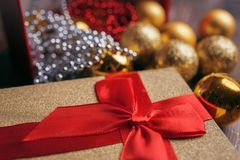 Christmas present on the background of gold balls and garlands Stock Image