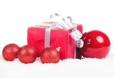 Christmas present and balls on snow Stock Image