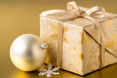 Christmas present and bauble on gold background Stock Photos