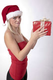 Christmas Present From A Blond Santa Girl. Beautiful Blond Girl With Santa Hat Holding A Christmas Present Stock Photos