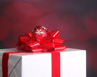 Christmas present with bow and ornament. Elegantly wrapped Christmas present with a red ribbon and snowflake ornament set against a festive holiday background Royalty Free Stock Images