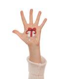 Christmas present box painted on kid's hand Stock Image