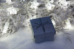 Christmas present box in snow with star lights Stock Images