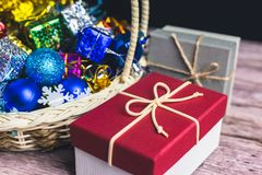 Christmas present box with some colorful paper and toys in basket on wood table stock photo