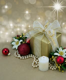 Christmas Present with candle and red baubles.. Beautifully wrapped present with candle and red baubles Stock Photo
