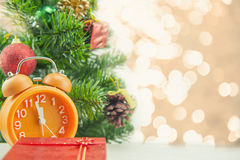 Christmas present celebration time orange clock and christmas tree. Royalty Free Stock Image