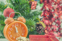 Christmas present celebration time orange clock and christmas tree. Royalty Free Stock Photo